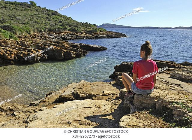 young woman sitting by a rocky inlet near Punta Negra on the North Coast, Menorca, Balearic Islands, Spain, Europe