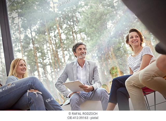 Smiling people talking in group therapy session