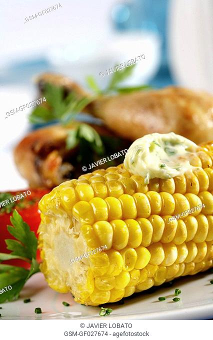 Grilled corn cob with roast chicken detail