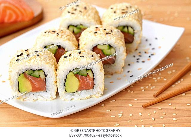 California roll sushi traditional Japanese rice food with salmon, avocado, cucumber, nori and sesame seeds. Healthy seafood meal