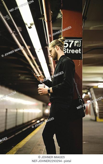 Man using smartphone in subway platform