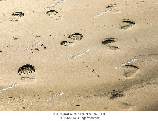 Walkers' footprints with shoes and barefoot, on a beach in Tregastel (France) on 29.09.2017. Photo: Jens Kalaene/dpa-Zentralbild/ZB | usage worldwide