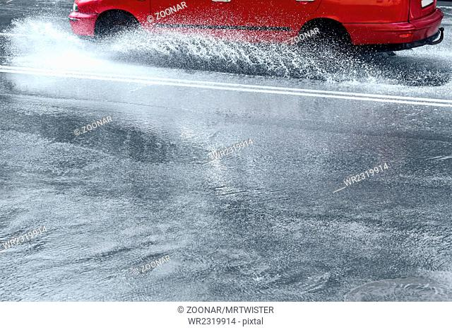 splashes by car through flood water