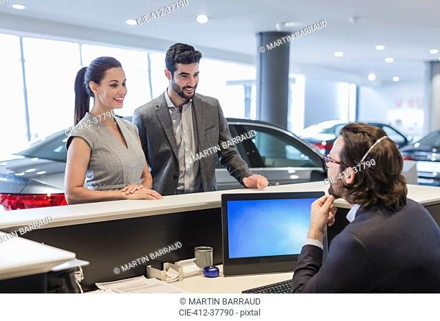 Couple customers talking to male receptionist at desk in car dealership showroom