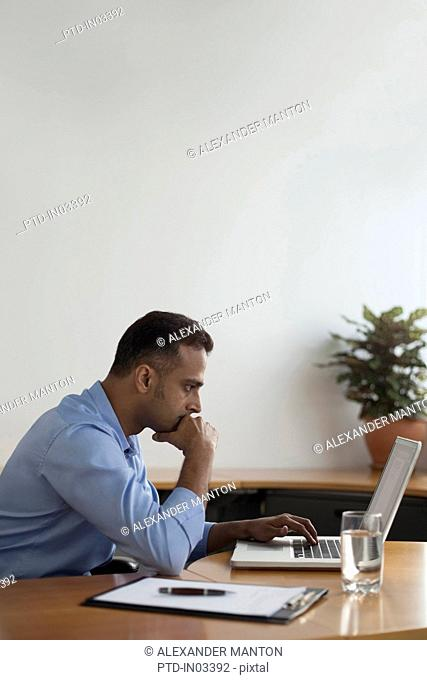 Singapore, Businessman using laptop in office