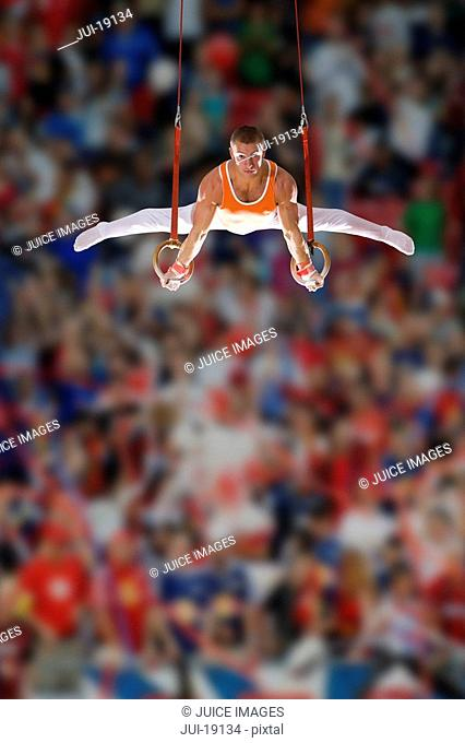 Male gymnast performing on gymnastic rings, low angle view