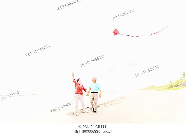 Couple flying kite together on beach