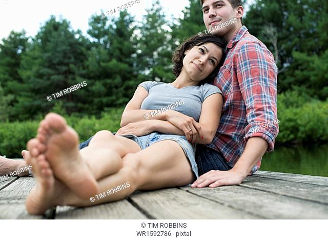 A couple relaxing on a jetty overlooking a mountain lake