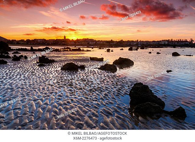 Rocky beach and village at dusk. Trengandin beach. Noja, Cantabria. Spain, Europe