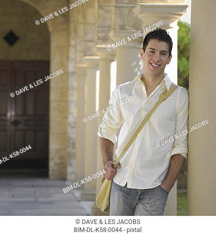 Male university student leaning on column, Perth, Australia