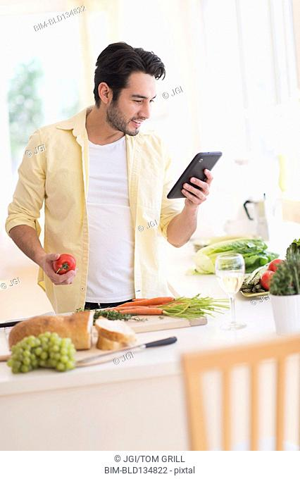 Mixed race man cooking with digital tablet in kitchen