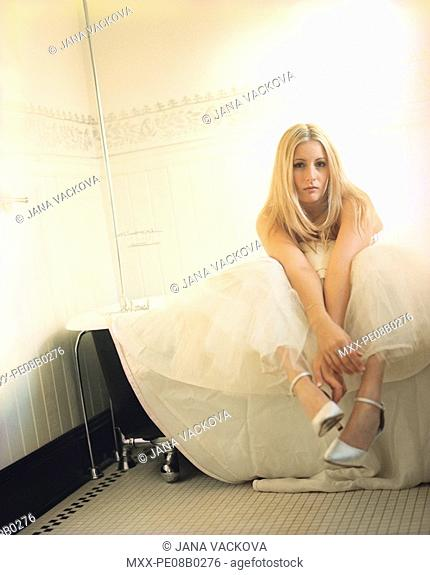 Bride sitting in a tub with legs and dress over the edge