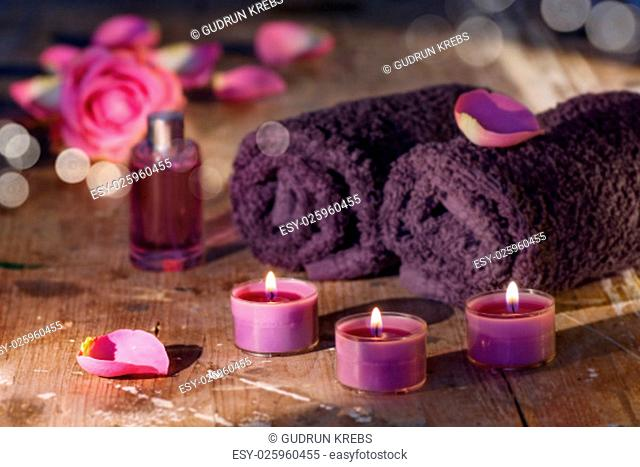rose essence with petals arranged on a wooden table