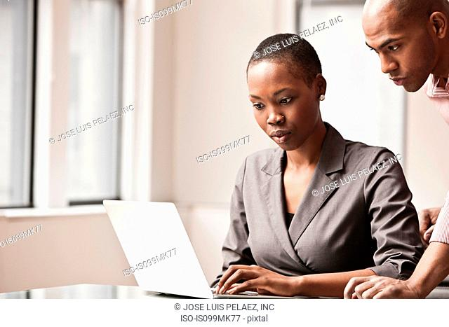 Two business colleagues using laptop
