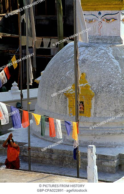 Nepal: A monk prays next to a small stupa at Bodhnath (Boudhanath), Kathmandu