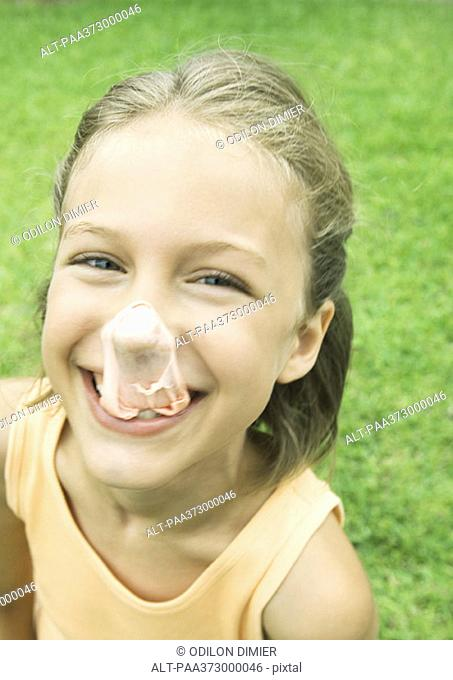 Girl with popped gum bubble on nose