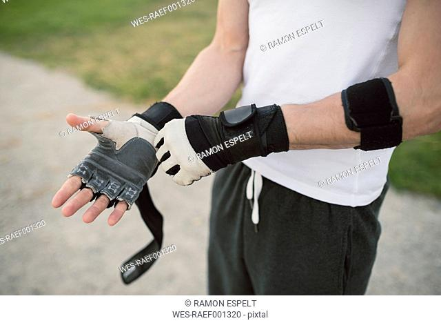 Young man putting on a training glove on the hand to train