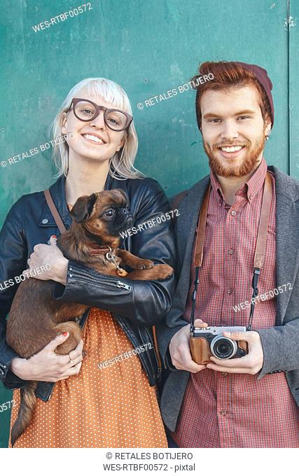 Portrait of smiling young couple holding a dog