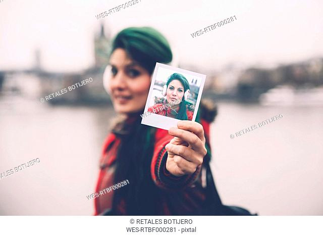 Germany, Cologne, woman showing polaroid of herself
