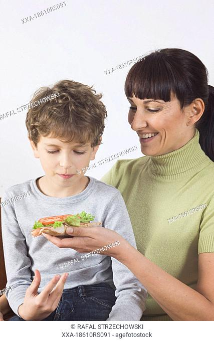 mother giving sandwich to son