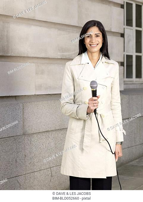 Hispanic female reporter holding microphone