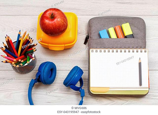 Headphones, color pencils, yellow lunch box, apple and open exercise book on bag-pencil case with color felt pens and marker on grey wooden boards