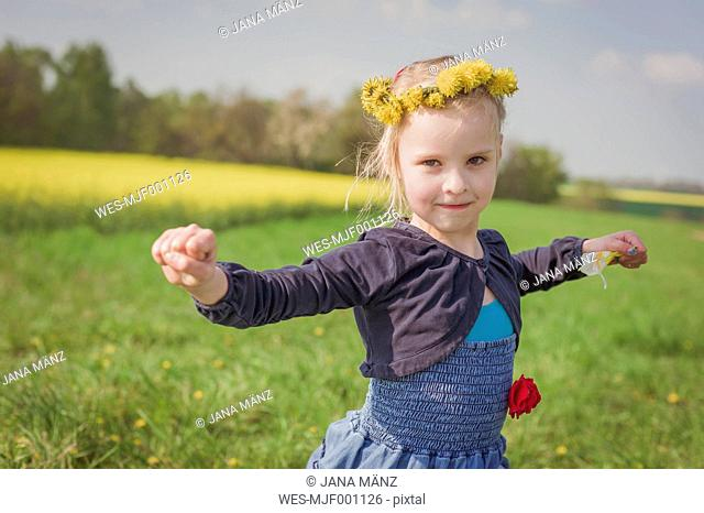 Little girl with outstretched arms standing on a meadow