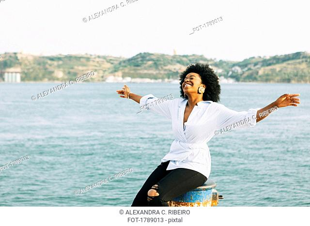 Carefree young woman with arms outstretched at waterfront, Belem, Lisbon, Portugal