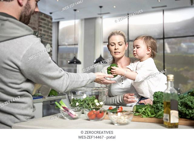 Family with baby preparing a healthy meal in kitchen
