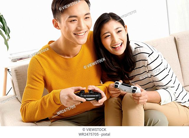 The young couple sat on the sofa and played games