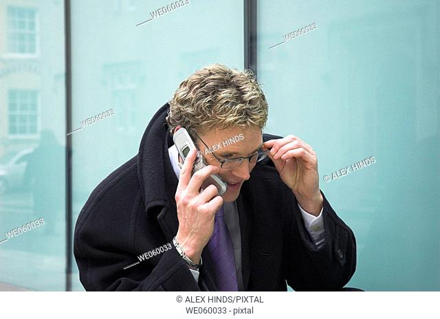 Young businessman outside talking on a mobile phone