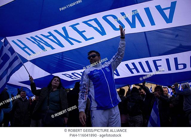 """Greeks under huge Greek flag, during protest rally against recognition of FYROM as North Macedonia. Writing """"""""Macedonia"""""""". 20.01"""