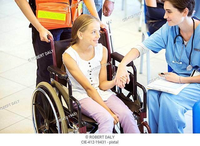 Nurse and patient holding hands in hospital