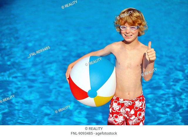 A boy with goggles and water ball in an open air bath