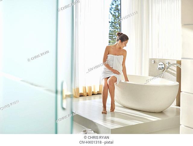 Woman wrapped in towel preparing a bath