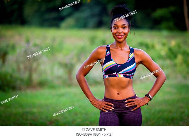 Portrait of young female runner with hands on hips in park
