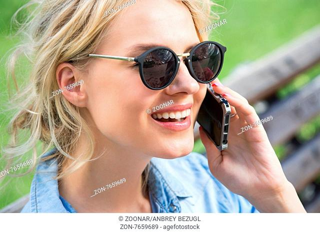 Closeup portrait of cute blonde in sunglasses and a bright blue denim shirt emotionally talking on a cell phone