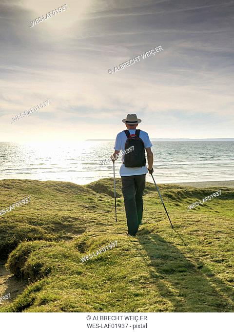 France, Bretagne, Active senior hiking on the beach of Treguer at sunset