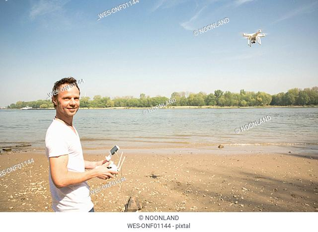 Portrait of smiling man flying drone at a river