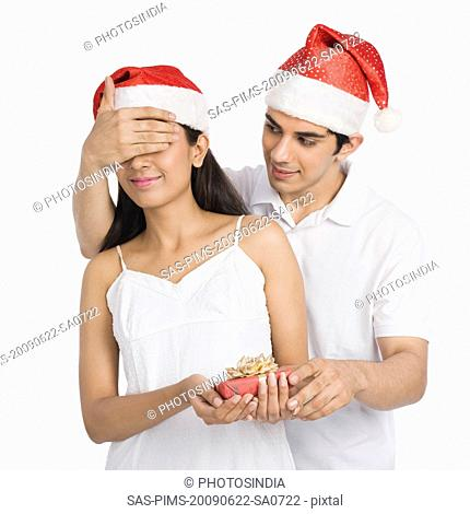 Man covering his girlfriend's eyes and giving a Christmas present