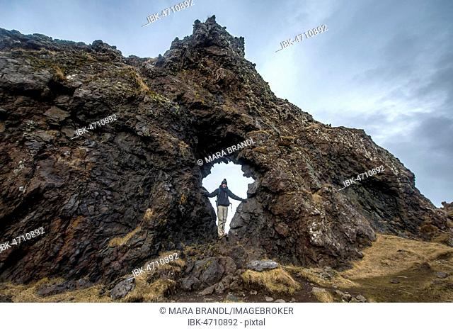 Young man stands in rock arch, volcanic rock on the beach of Djúpalónssandur, Snæfellsnes peninsula, West Iceland, Iceland