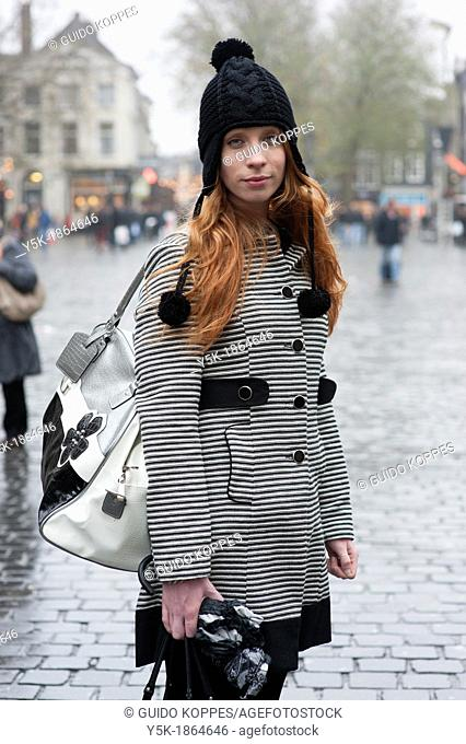Breda, Netherlands. Young, fashionable and redheaded woman, standing on a city square